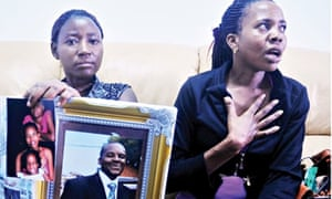 Mariam Nabanja, right, and her sister Emily with a photograph of husband Ham Andrew Ngobi in Kampala