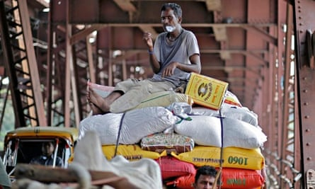 Worker sitting on a cart carrying rice sacks