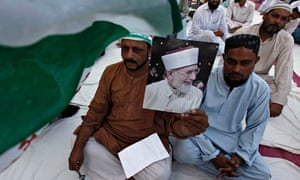 A supporter holds an image of Tahir-ul-Qadri, leader of Pakistan Awami Tehreek, at a gathering in re