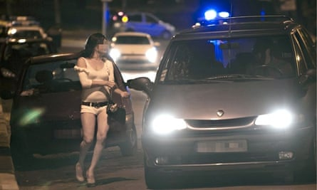 A prostitute about to talk to a man in a car