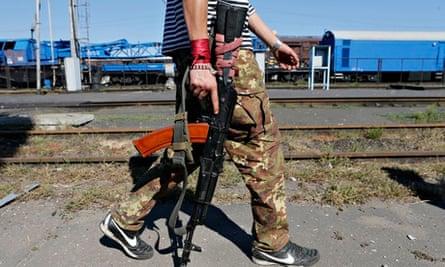 A pro-Russian separatist walks along a railroad station in the eastern Ukrainian town of Ilovaysk