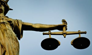 A statue holding the scales of justice is seen on top of the Old Bailey, London