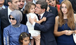 Turkey's prime minister, Ahmet Davutoglu, kisses the daughter of the country's consul after her rele