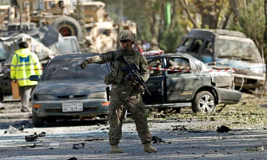 A US soldier guards the site of a suicide attack in Kabul, Afghanistan