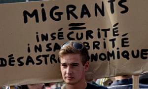 A protester in Calais with a banner that reads: 'Migrants equal insecurity, unhealthiness and econom