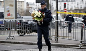 TOPSHOTS A policeman carries flowers bro