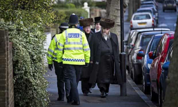Policemen and Jewish men walking down the street