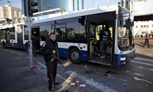An Israeli police officer secures the scene after a suspected terrorist attack on a bus in Tel Aviv