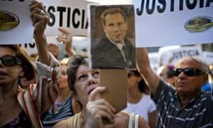 A protester holds aloft a portrait of the late prosecutor Alberto Nisman