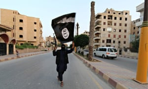 A member loyal to the Islamic State in Iraq and the Levant (ISIL) waves an ISIL flag in Raqqa