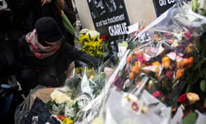 A woman adds her floral tribute outside the Charlie Hebdo headquarters