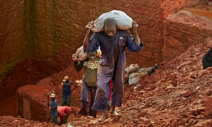 Diamond miners carry bags of earth from their concession near an Angolan village
