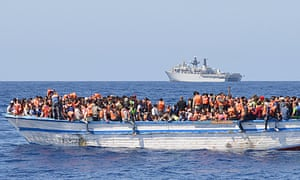 Migrants in a wooden-hulled ship wearing lifejackets provided by HMS Bulwark, seen in the background