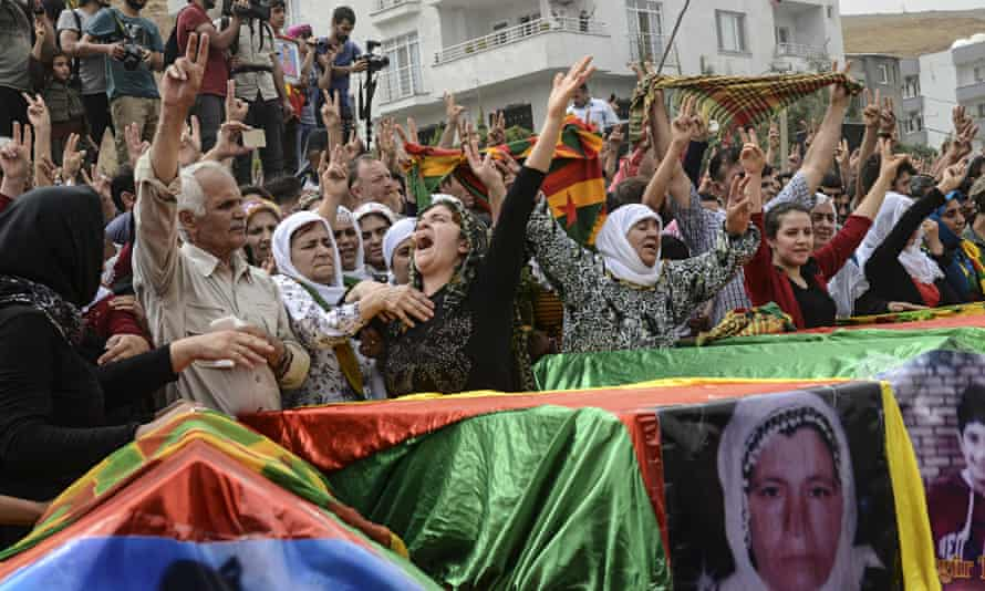 Coffins are draped in the Kurdish flag,