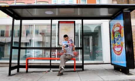 Person reading Time Out magazine at a bus stop