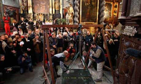 Archeologists lift the tombstone of Tycho Brahe at a church in Prague.