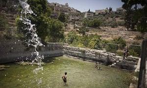 Palestinian children swim in the ancient spring in the West Bank village of Battir