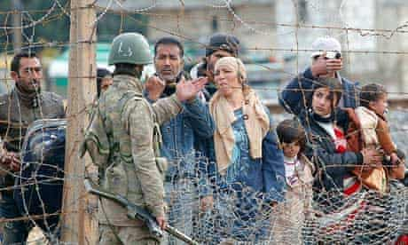 Syrians plead with a Turkish soldier as they try to cross the border from Ras al-Ain in Syria