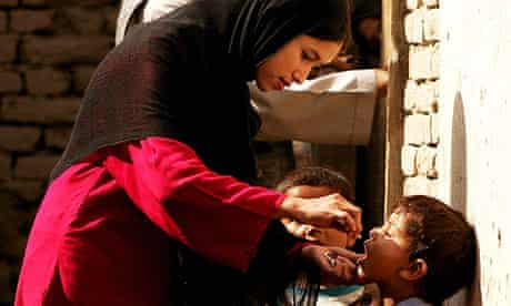 A health worker gives a dose of polio vaccine to a child in Afghanistan
