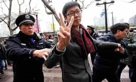 A man gestures as Shanghai police break up Jasmine Revolution protests inspired by the Arab spring