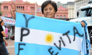 A woman holds an Argentinian flag at the presidential palace