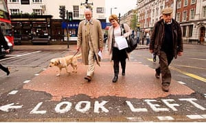 London mayoral candidate Ken Livingstone (L) walks his dog Coco as he meets voters in north London