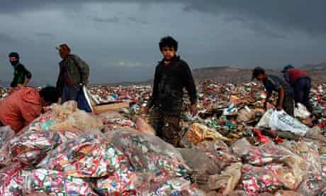 A child scratches for anything to recycle in a rubbish dump