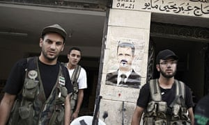 Syrian rebels before a poster of President Bashar al-Assad made into a devil caricature in Aleppo