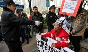 A policeman confronts a protester in a wheelchair outside the Southern Weekly newspaper in Guangzhou