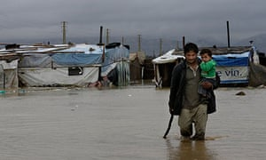 A Syrian refugee carries his child as he wades through floodwater at a refugee camp in Lebanon
