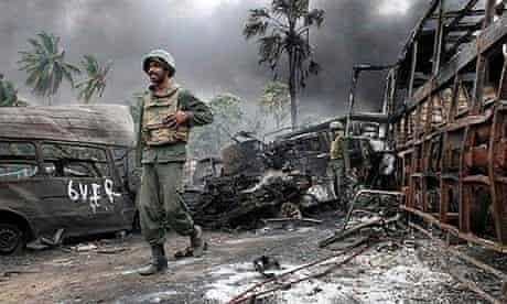 Sri Lankan troops walking amongst debris inside the war zone on May 17,
