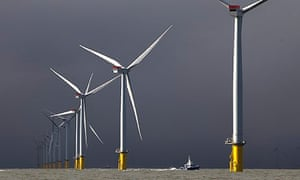A ship passes between wind turbines at the London Array, a Round-2 windfarm.