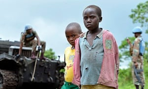 Children by a burnt-out tank abandoned by M23 rebels in Kimbumba as UN took control of east Congo