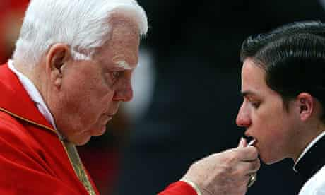 Cardinal Bernard Francis Law, left, gives communion to a young seminarist in the Vatican.