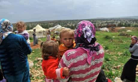 A Syrian refugee carries her children near the Turkish border.