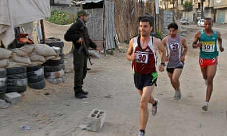 Palestinian runners pass a Hamas security officer in Beit Lahiya, Gaza, in the first Gaza marathon.