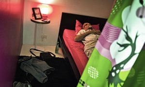 A man sleeps in a capsule of a hotel for A 'capsule hotel' designed by Ikea on a French motorway