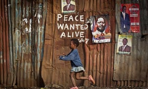 A girl runs past graffiti written during violence that after 2007 election and Raila Odinga  poster