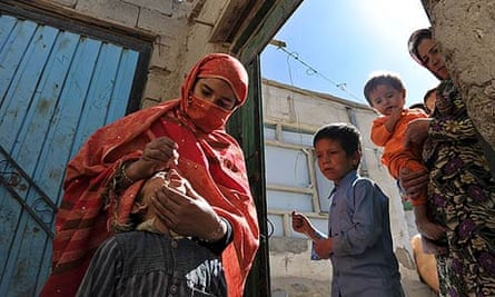 An Afghan health worker administers polio vaccine to a child.