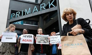 A shopper passes protesters outside a branch of Primark, which was supplied from the factory