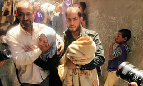 A Palestinian boy mourns as men comfort a relative at Hitham Masshal's funeral in Shati refugee camp