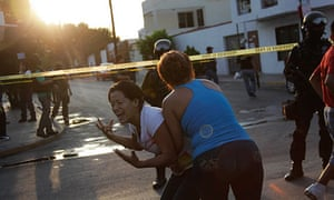 A woman is held back she reacts to the Gulf cartel's killing of three men and a woman in Monterrey