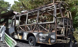 Pakistani police inspect a student bus bombed by Sunni Islamist militants
