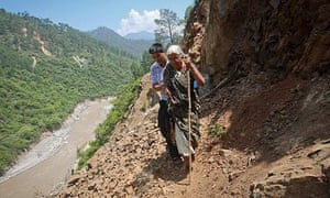 A pilgrim is helped by a villager along a path damaged by a landslide in the state of Uttarakhand