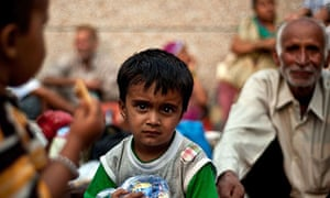 An Indian boy rescued from flood-hit Uttarakhand waits before going to Dehradun relief camps