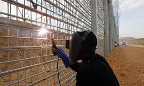 Sudanese illegal immigrant, who crossed from Egypt to Israel, building a fence to keep out migrants