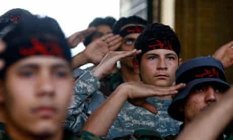 Iraqi Shia fighters salute the shrine of Sayyida Zeinab in Damascus.