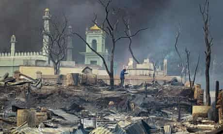 A man stands in front of a mosque as it burns in Meikhtila after the riots in March.