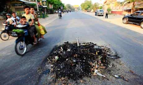 People ride their mopeds past the remains of two persons killed in clashes in Meikhtila in March