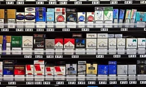 Packets of cigarettes in a shop. The government announced it had postponed plans for plain packaging